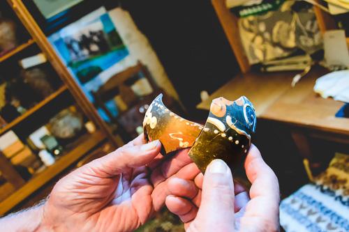 Scherben römischer Weinamphore aus Weinberg Graacher Himmelreich in Hand; Büro im Hintergrund