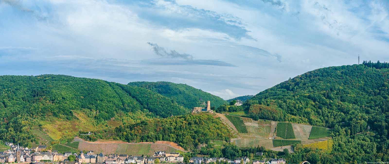 Am unteren Rand liegt der Ort Bernkastel-Kues. Über dem Ort liegen Weinberge, Wälder und Himmel. In der Mitte befindet sich die Burg Landshut. Unterhalb der Burg Landshut liegt der Bernkasteler Schloßberg.