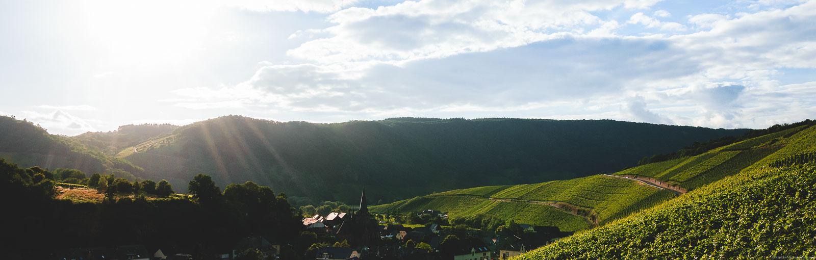 Sonnenuntergang an der Mosel. Links vorne ist ein Felsen. In der Mitte im Tal ist der Ort Neumagen-Dhron mit einer Kirche. Rechts liegt der Weinberg Dhroner Hofberger. Oben sind große Wolken.