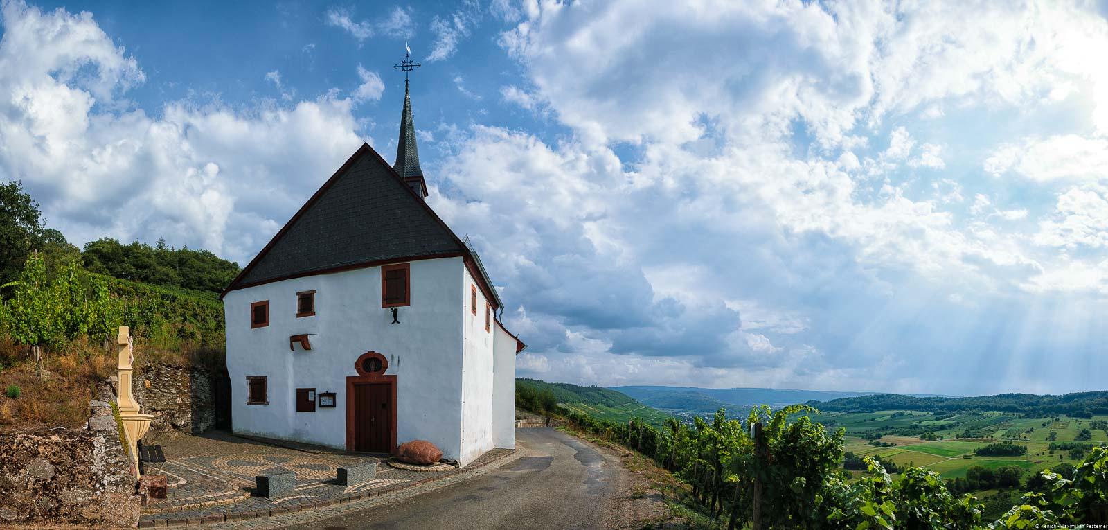 Auf dem Schlossberg bei Lieser befindet sich eine alte Kapelle. Unten breitet sich die Ebene vor dem Dorf aus. Am Himmel sind Wolken aus den Sonnenstrahlen auf den Boden strahlen. Der Weinberg liegt im Bereich der Mittelmosel.