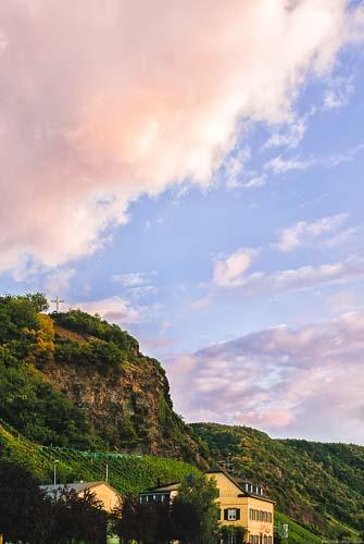 Es ist ein Weingut und der Weinberg Wintricher Großer Herrgott mit einem Kreuz am Sonnenuntergang erkennbar. Am Ende des Weinbergs liegt der Weinberg Wintricher Ohligsberg.