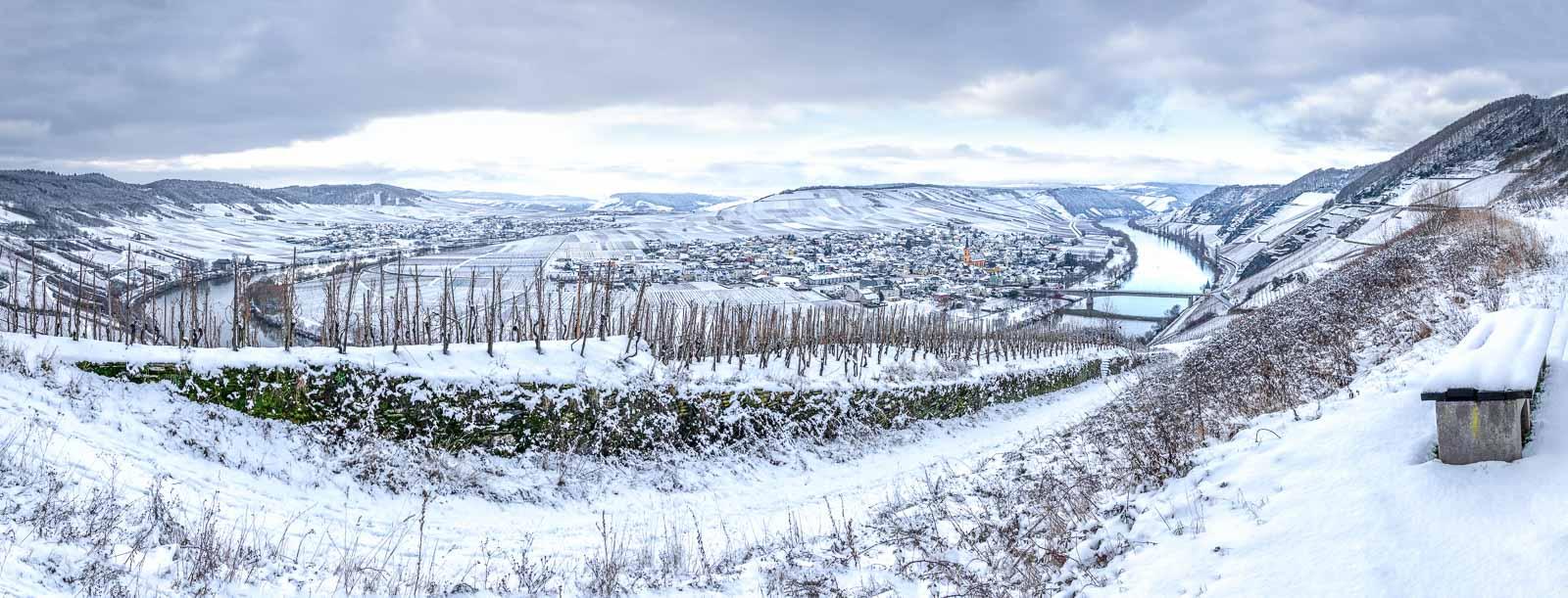Im Winter ist der Weinberg beim Ort Trittenheim an der Mosel mit Schnee bedeckt. In der Sektion unter dem Bild erfährst du mehr über Vinaet und die Dienstleistungen für das Marketing.