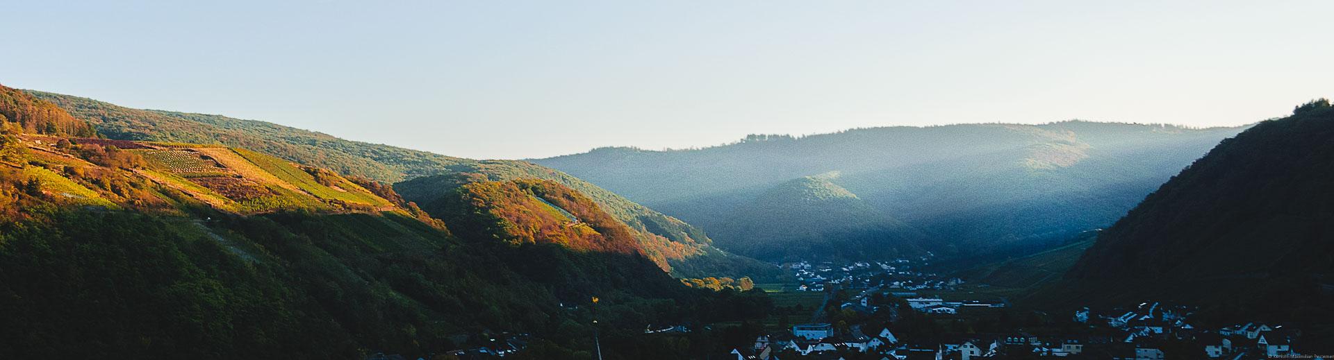 Sonnenstrahlen strahlen Abends seitlich in das Ahrtal auf den Weinberg Dernauer Goldkaul. Im Hintergrund erblickt man den Ort Rech. Die Hügel an beiden Seiten des Tales sind bewaldet.