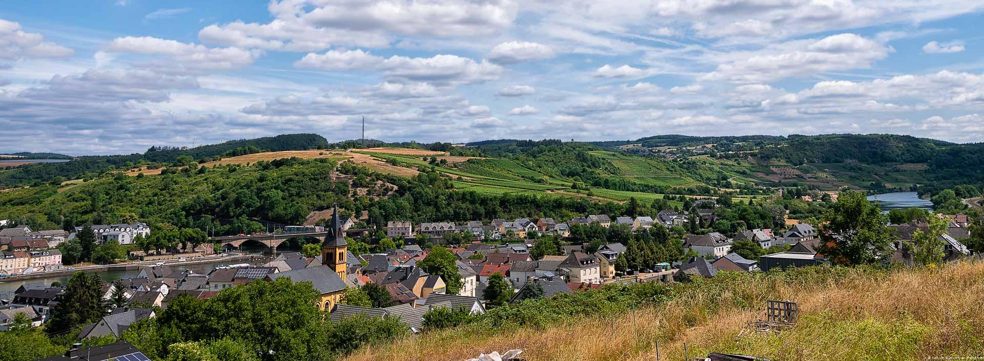 Blick auf Weinberge wie zum Beispiel der Langsurer Brüderberg an der Obermosel. Vorne im Tal fließt der Fluss Mosel. Am gegenüberliegenden Ufer der Mosel liegt der Ort Wasserbillig. Am blauen Himmel sind viele Wolken.