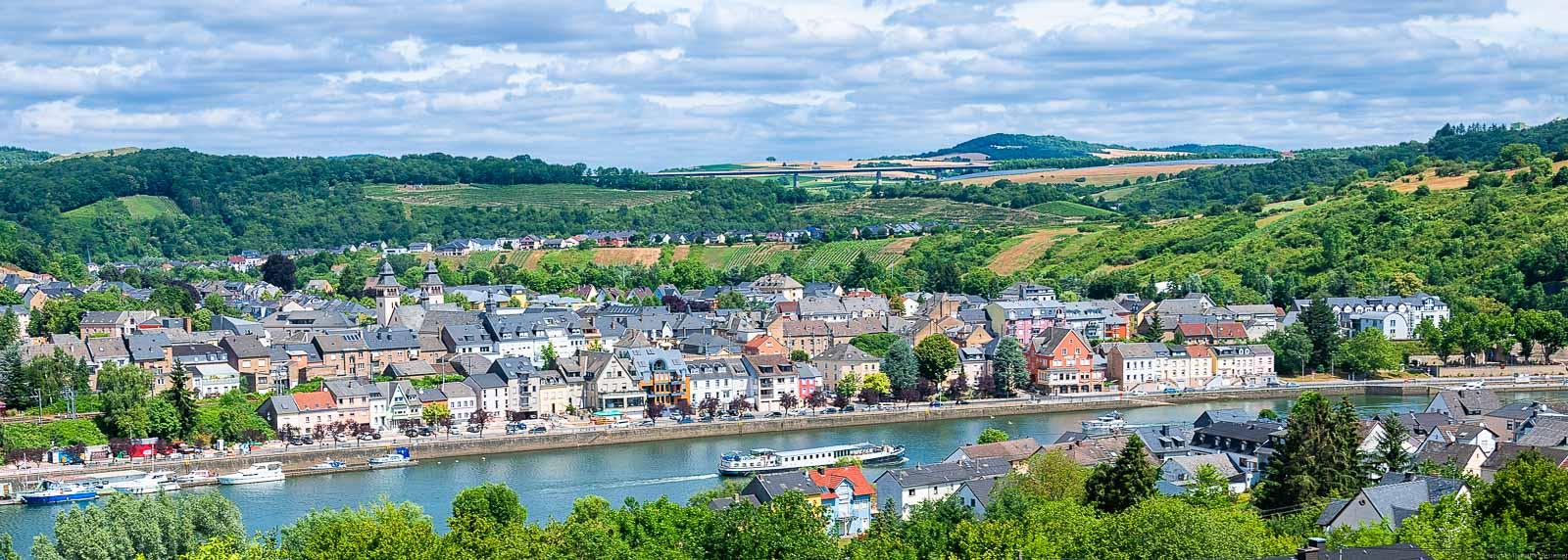 Im Vordergrund fließt die Mosel. Am anderen Ufer liegt der Ort Luxemburg. Im Hintergrund liegen Weinberge. Man erkennt hinter dem Ort Wasserbillig den Langsurer Brüderberg am Ufer des Flusses Sauer. Der Himmel ist bewölkt.