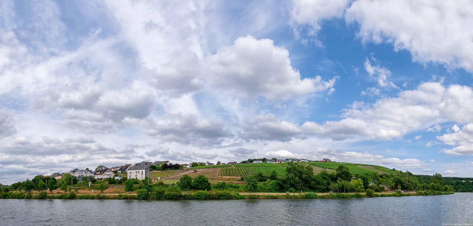 Weinberg und Ort an Ufer des Flusses Mosel und blauer Himmel mit Wolken
