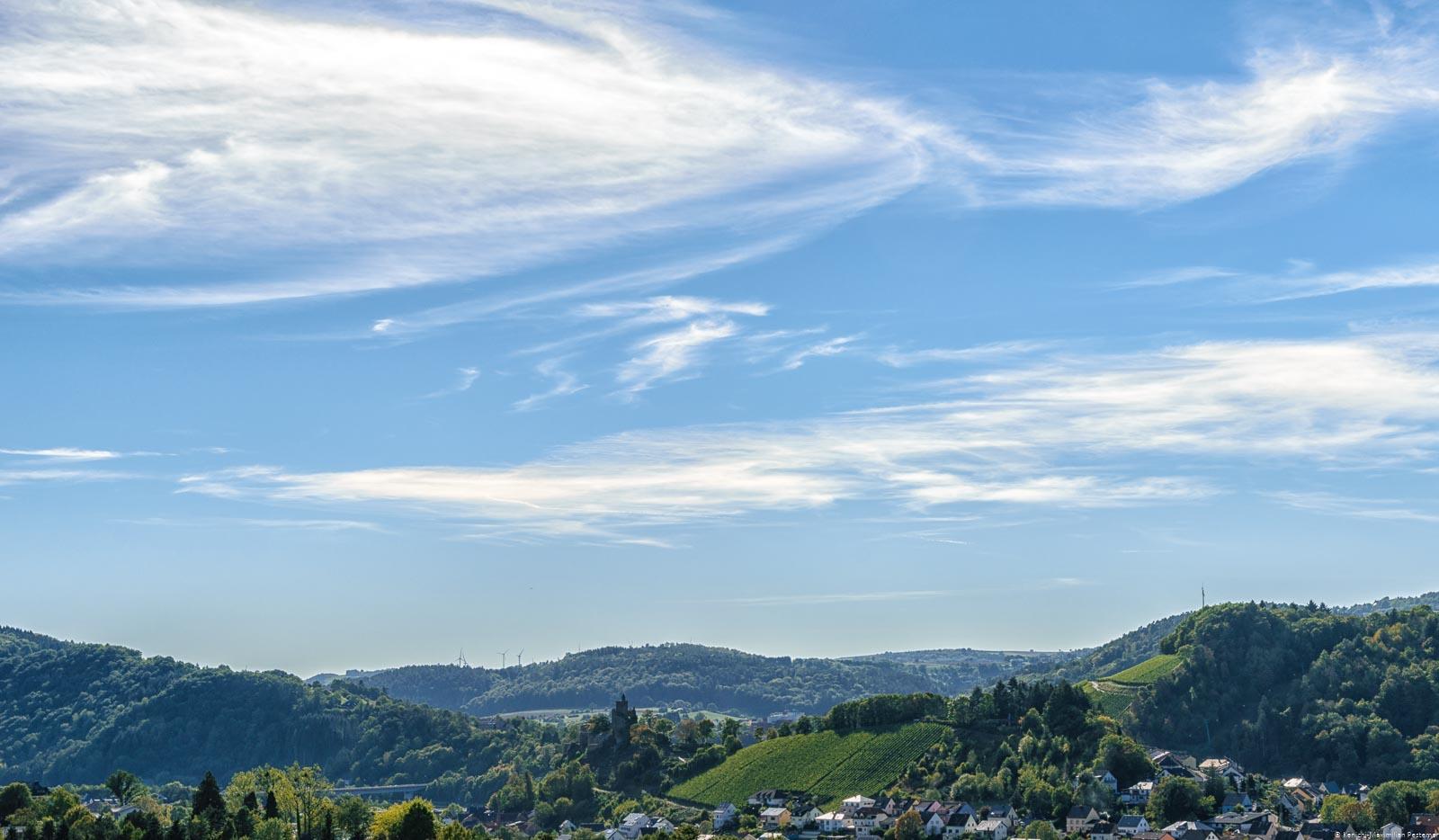 Aussicht auf den Ort Saarburg, den Fluss und die Weinberge. Man erkennt rechts den Ort Niederleuken. In der Mitte erkennt man die Saarburg und den Weinberg Saarburger Schlossberg daneben. Im Hintergrund sind bewaldete Hügel. Am blauem Himmel fliegen einige weiße Wolken.