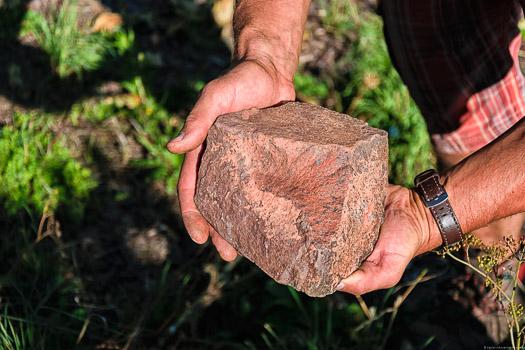 Das rote Gestein des Weinbergs an der Saar ist sehr eisenhaltig. Der Stein befindet sich in den Händen vom Winzer Cord Treseler.