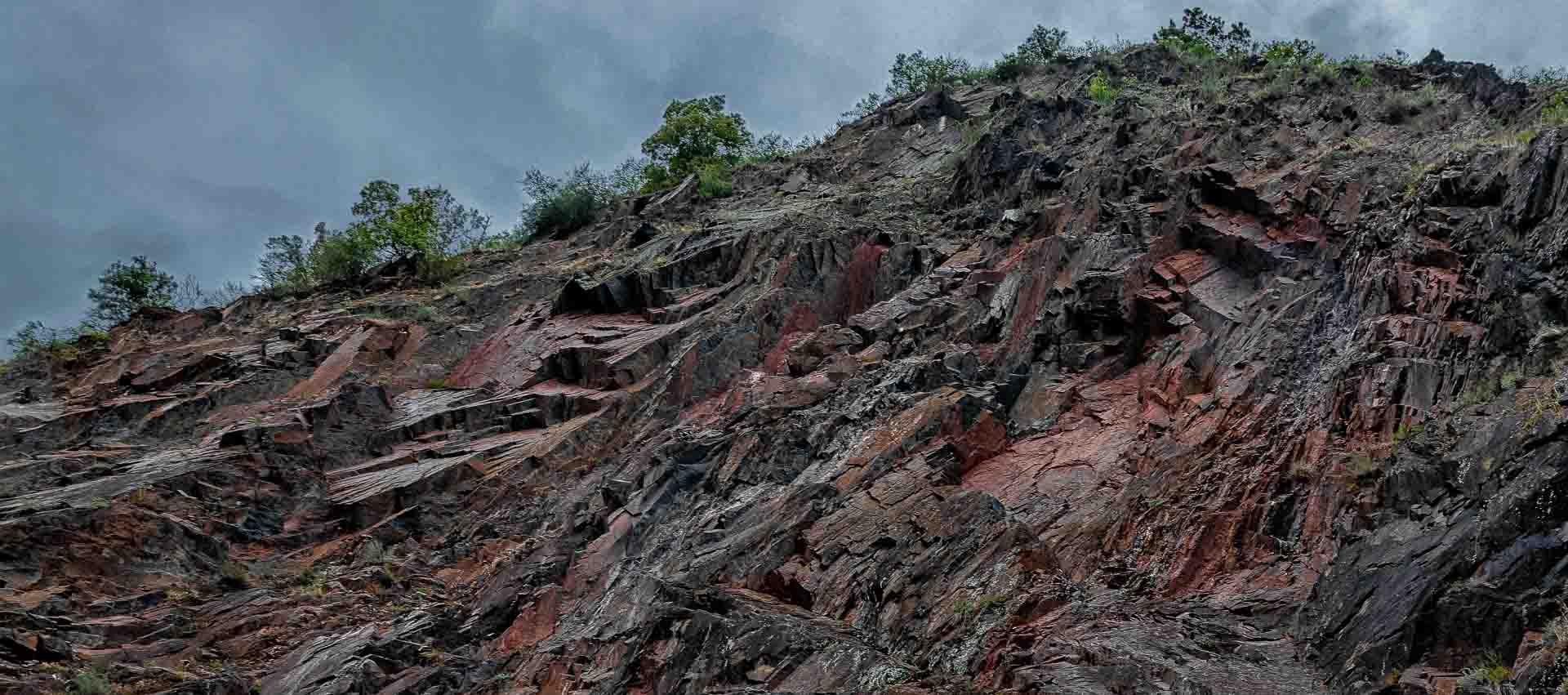 Neefer Frauenberg Mosel Fels aus rotem und blauen Schiefer mit Wolken am Himmel