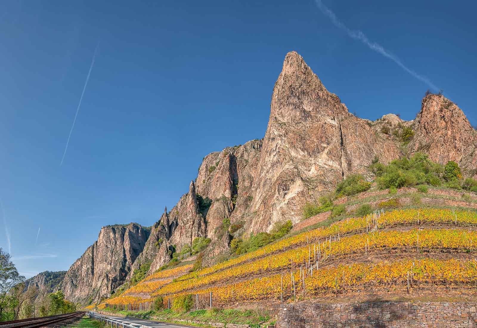 Die Traiser Bastei liegt unterhalb des Rotenfels bei Bad Münster. Vorne links verläuft eine Straße neben Bahngleisen. Unter den spitzen Felsen liegt der Weinberg. Die Himmel ist blau.