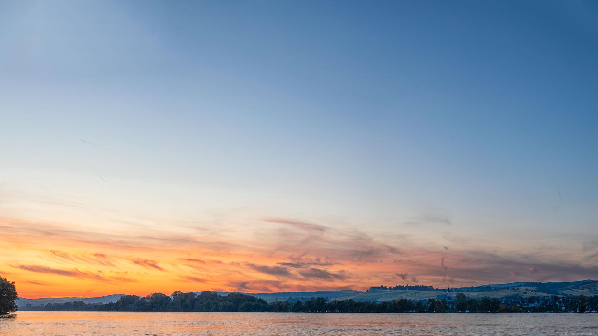 Feuriger Sonnenuntergang bei Oestrich-Winkel am Rheingau. Vorne unten im Bild verläuft der Fluss Rhein. Am anderen Ufer erkennt man Bäume, Häuser und Weinberge des Rheingaus. Im Hintergrund erblickt man das Schloss Johannisberg- Der Himmel ist orange, rot und blau.
