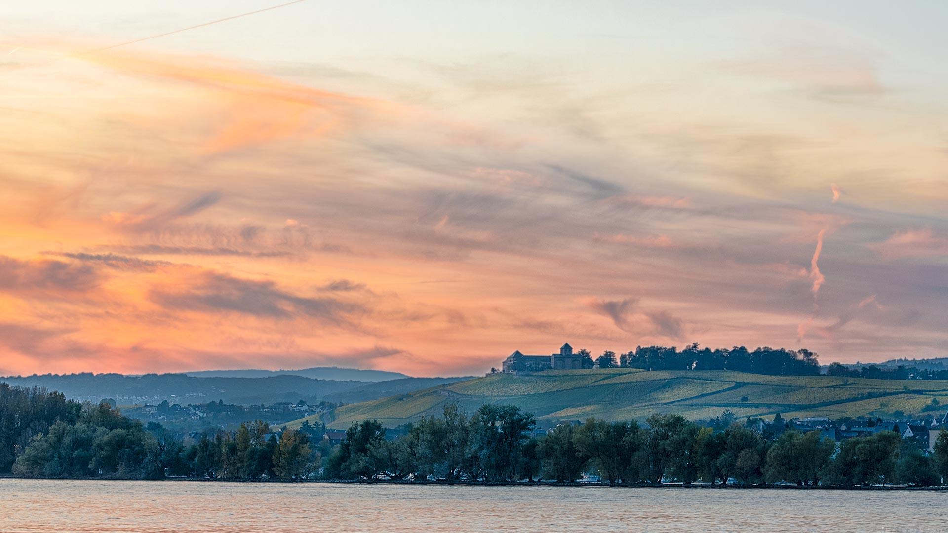 Fluss Rhein im Vordergrund, Ufer mit Bäumen und Ort Oestrich-Weinkel, Weinberg mit herbstlicher Färbung dahiner, Gebäude auf Weinberg, feurig roter Himmel am späten Abend