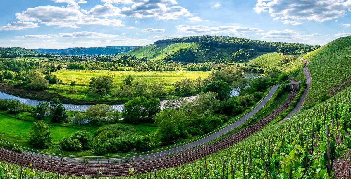 Mitten im Bild biegt sich die Saarschleife. Vorne sind Weinberge und Gleise sowie eine Straße. Am anderen Ufer sind Wiesen, Wälder und der Ort Kanzem. Im Hintergrund liegen weitere Weinberge sowie bewaldete Hügel. Der Himmel ist blau und etwas bewölkt.