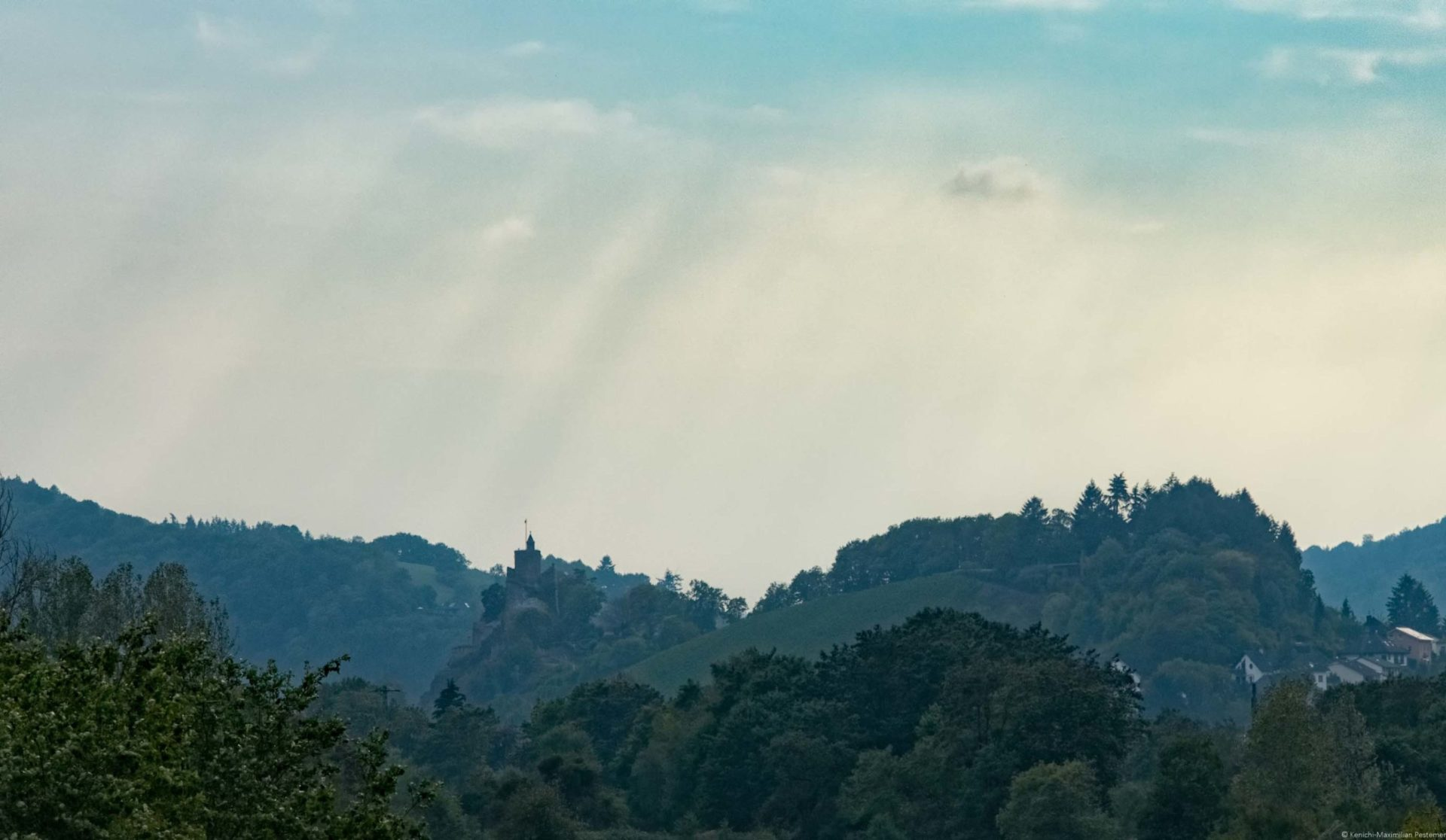 Saarburg mit Wald und Weinberg sowie Regenwolken am Himmel