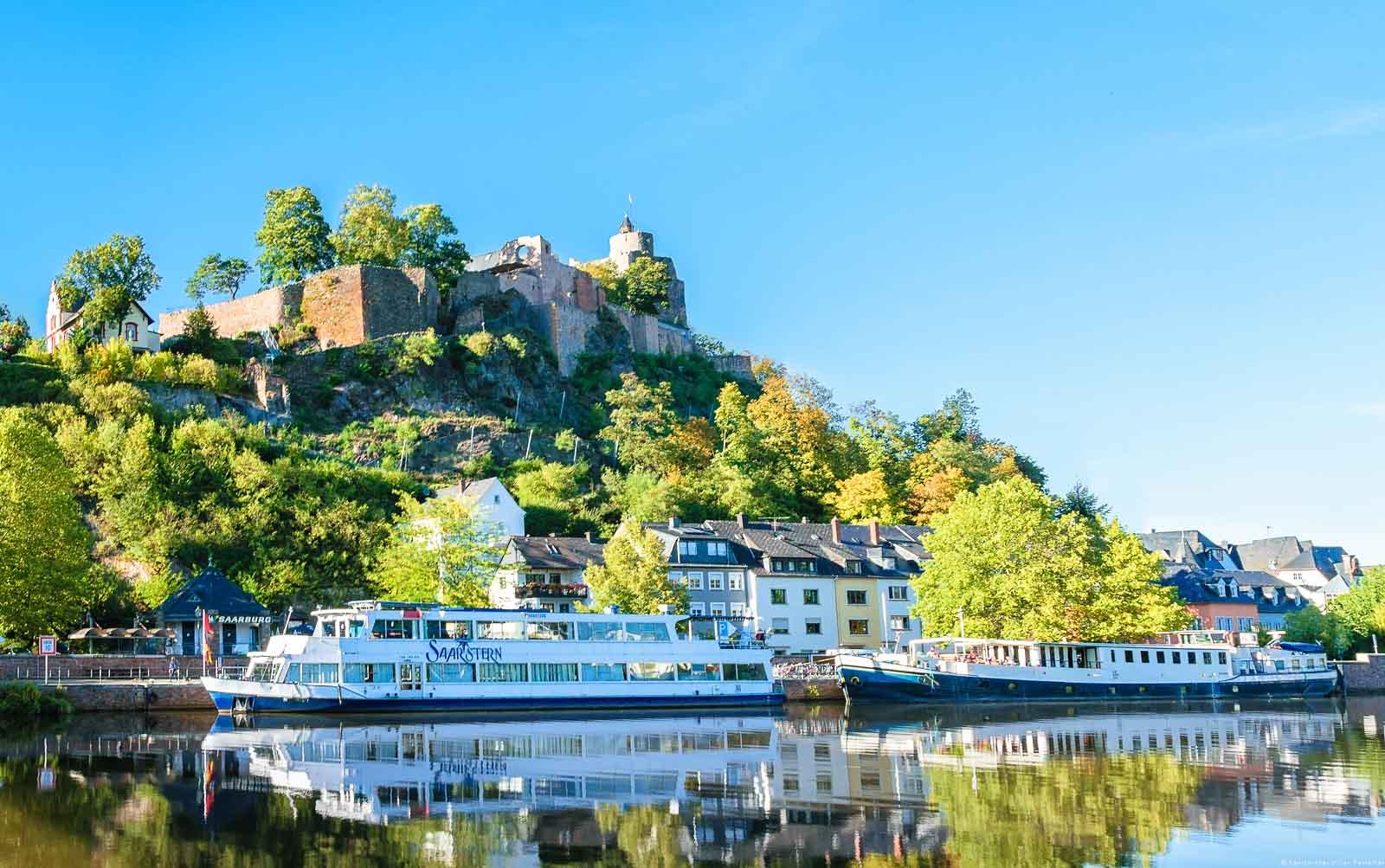 Vorne fließt der Fluss Saar. Am anderen Ufer ist ein Schiff. Dahinter befinden sich Häuser der Stadt Saarburg und ein Schloss auf einem steilen bewaldeten Hügel. Der Himmel ist oben blau.