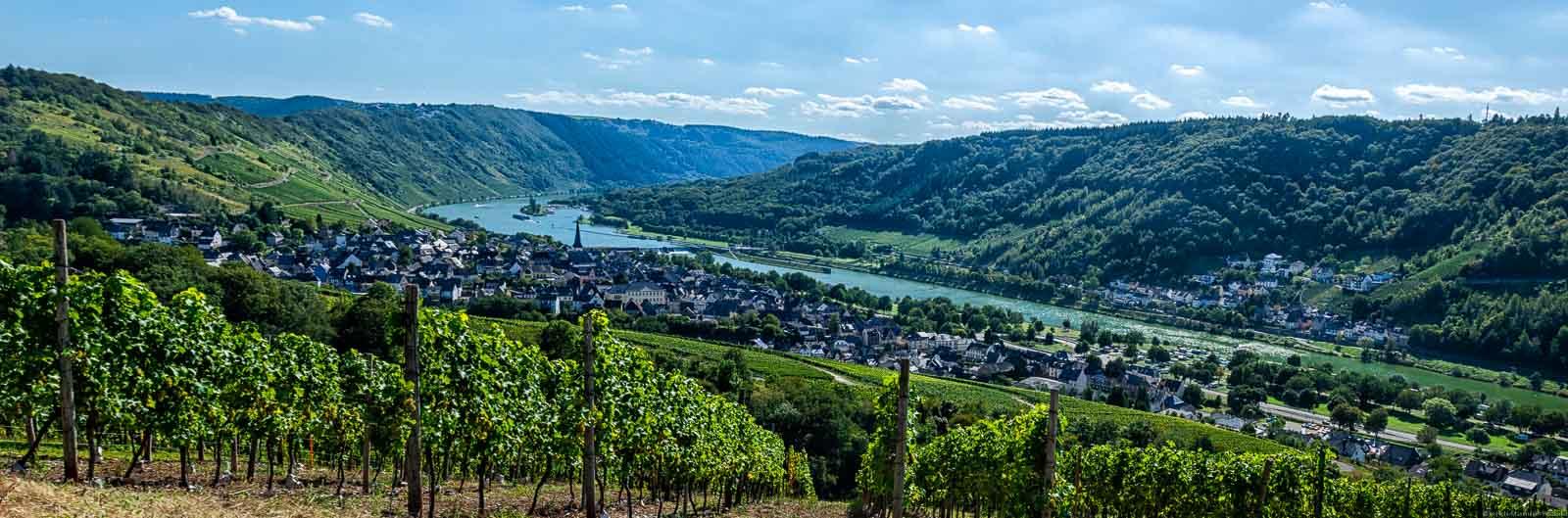 Bei den Orten Enkirch im Vordergrund und Kövenig im Hintergrund gibt es ein tolles Moselpanorama hinter dem Weinberg Enkircher Monteneubel. Zwischen den Orten fließt die Mosel. Im Hintergrund erkennt man weitere Weinberge und bewaldete Hänge. Der Himmel ist blau mit einigen Wolken.