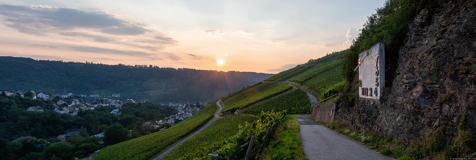 Vom Enkircher Steffensberg beim Ort Enkirch kann man tolle Sonnenuntergänge genießen. Vorne sind Weinberge. Rechts verläuft ein Weg unterhalb eines Felsens mit einer Sonnenuhr. Unten links ist ein Dorf. Im Hingergrund sind die Sonne, der Himmel und Wolken.