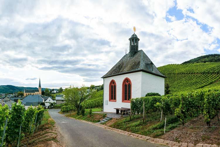 Kleine Kapelle im Weinberg Kröver Letterlay mit Ort Kröv im Hintergrund und bewölktem Himmel