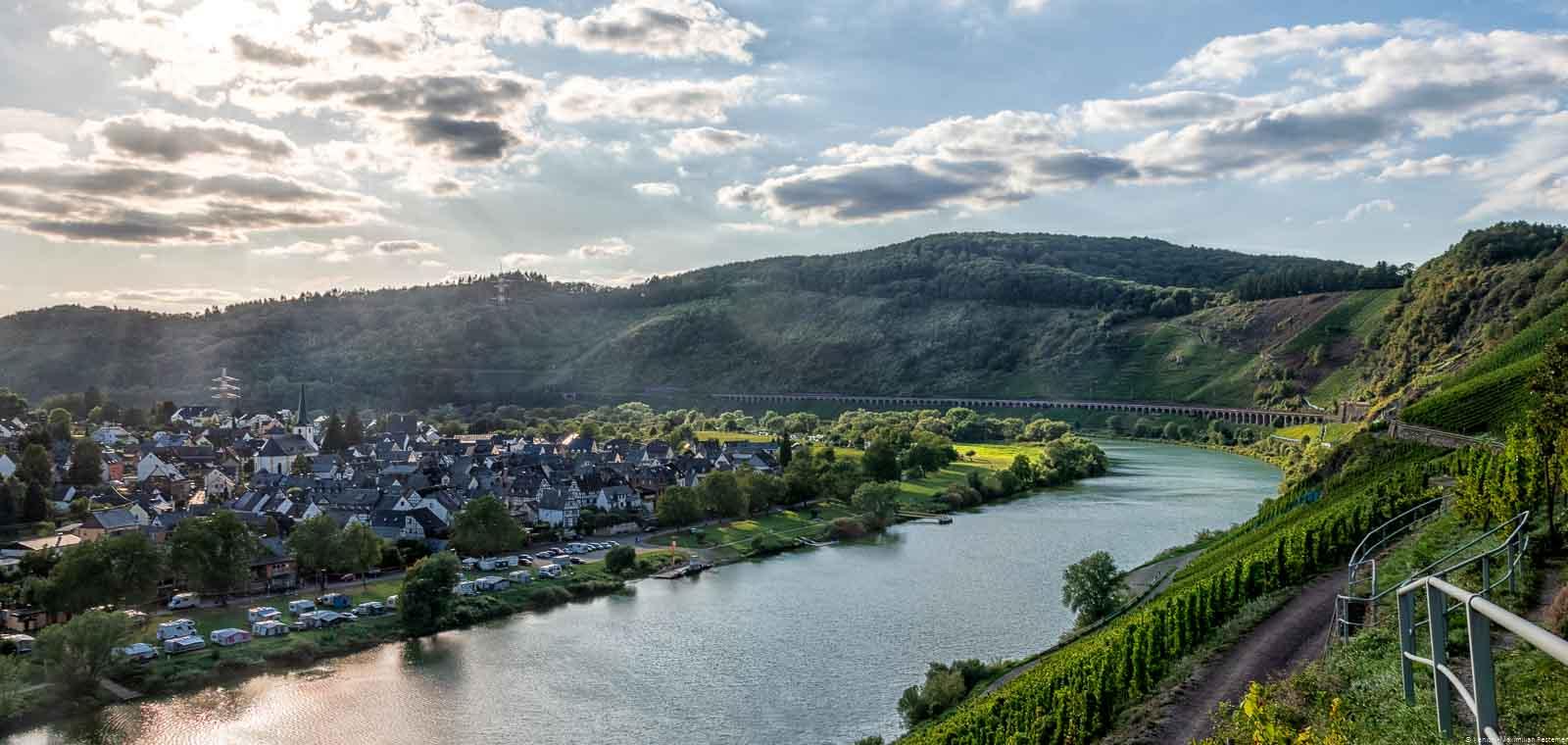 Der Ort Pünderich befindet sich innerhalb einer Biegung der Mosel. Am anderen Ufer liegt der Weinberg Pündericher Marienburg.