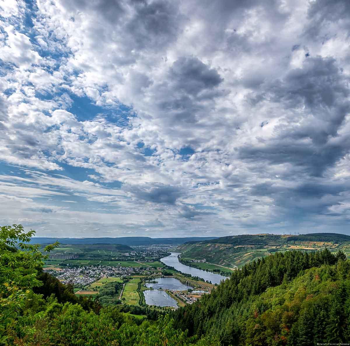 Ausblick vom Mittelgebirge des Hunsrück auf Moseltal und die Weinberge. Es ist der Fünfseenblick an der Mittelmosel. Man blickt auch die Orte Riol und Longuich. Am Himmel sind Wolken.