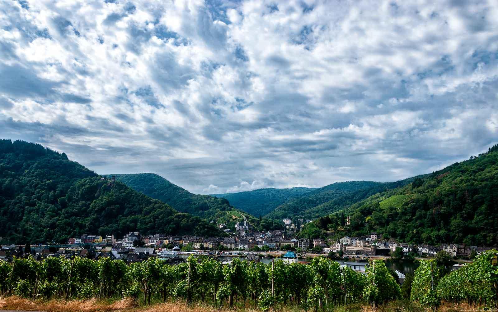 Die Altstadt von Traben-Trarbach ist geprägt vom Jugendstil. Im Hintergrund erkennt man den Trarbacher Burgberg und den Trarbacher Schlossberg.Die Mosel fließt durch den Ort. Der Himmel ist stark bewölkt. Die Doppelstadt liegt im Bereich der Mittelmosel.