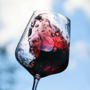 Rotweinglas vor blauem Himmel mit Wolke