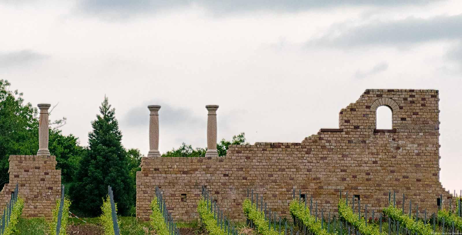 Ruinen von altem römischem Weingut bzw. alter Römervilla am Weilberg in der Pfalz mit Weinberg und bewölktem Himmel. Dort wurden einst vermutlichen eingige der ersten Pfalzweine hergestellt.