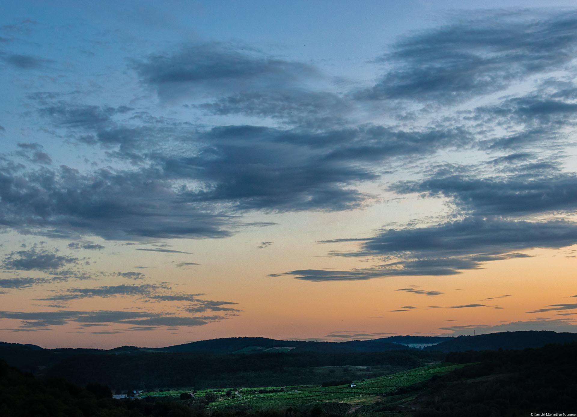 Man blickt aus der Ferne auf den Weinberg Wiltinger Schlangengraben. Rund um den Weinberg erkennt man bewaldete Hügel. Im Weinberg sind einige kleine Häuser. Links im Bild befindet sich der Fluss Saar. Am Himmel geht die Sonne unter. Der Himmel ist orange-rot und blau. Es sind Wolken am Himmel.