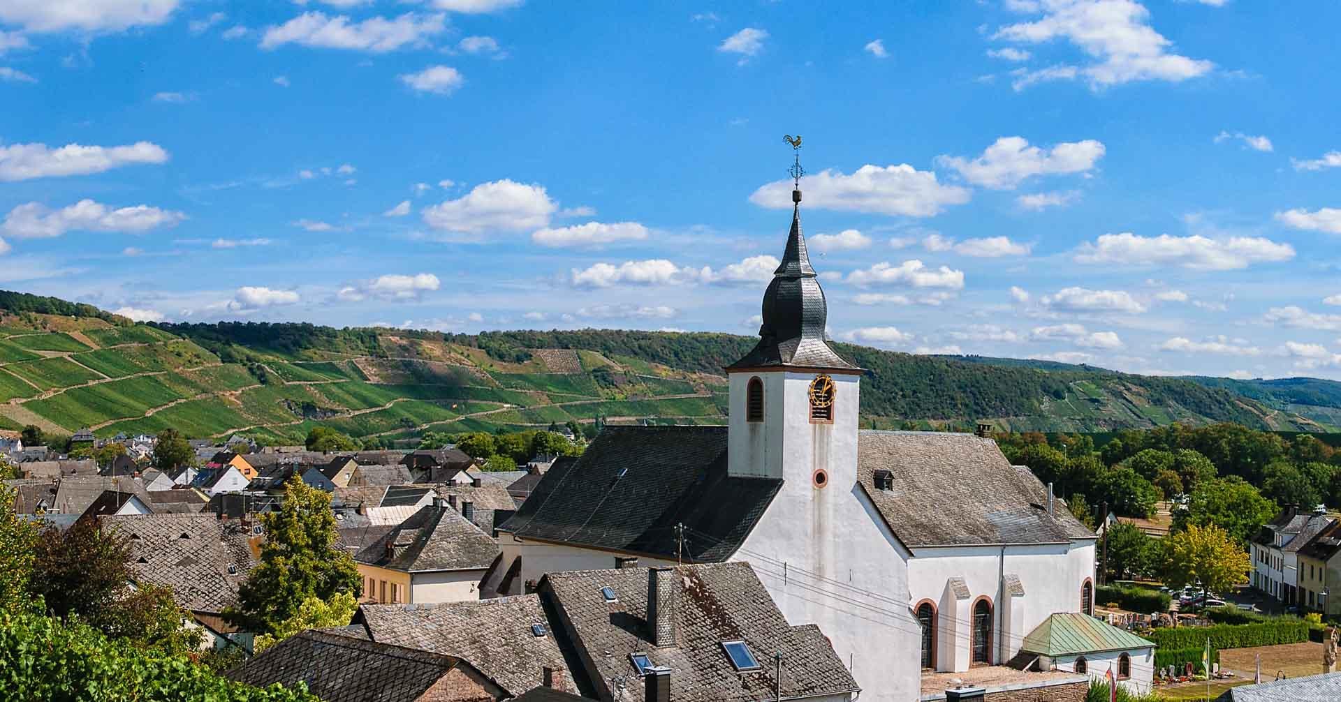 Man erkennt die Kirche des Ortes Klüsserath an der Mosel und den Weinberge Klüsserather Bruderschaft im Hintergrund. Es sind weitere Häuser erkennbar. Der blaue Himmel ist ganz leicht bewölkt.