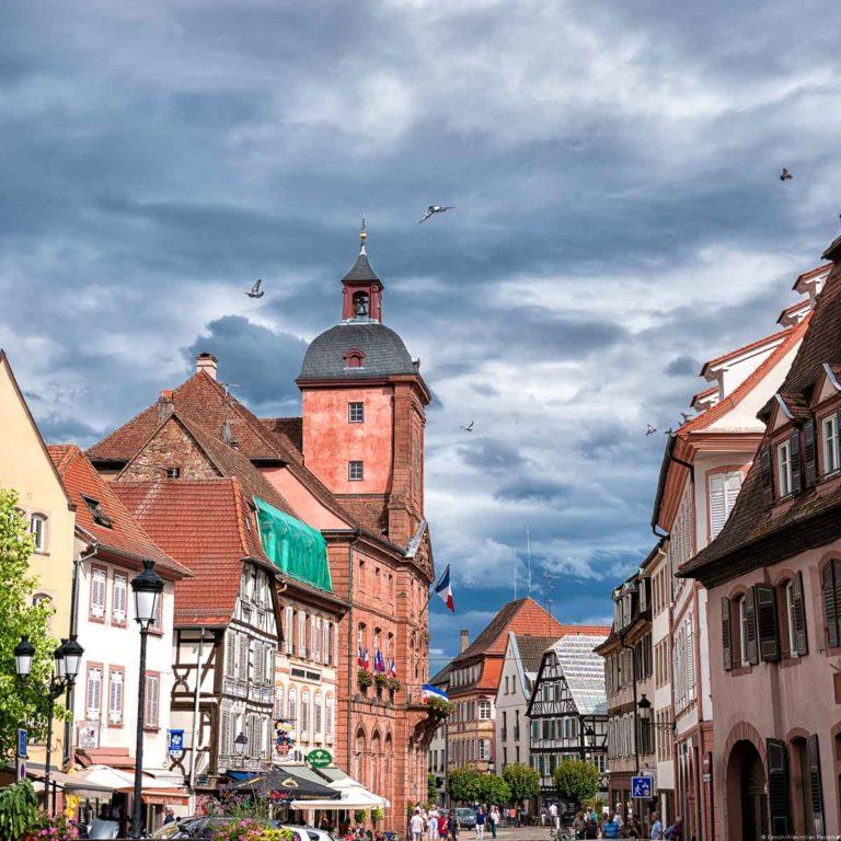 Straßen in der Stadt Weißenburg, welche in Frankreich Wissembourg genannt wird. Am Himmel sind Wolken. Es ist eine lebhafte Promenade