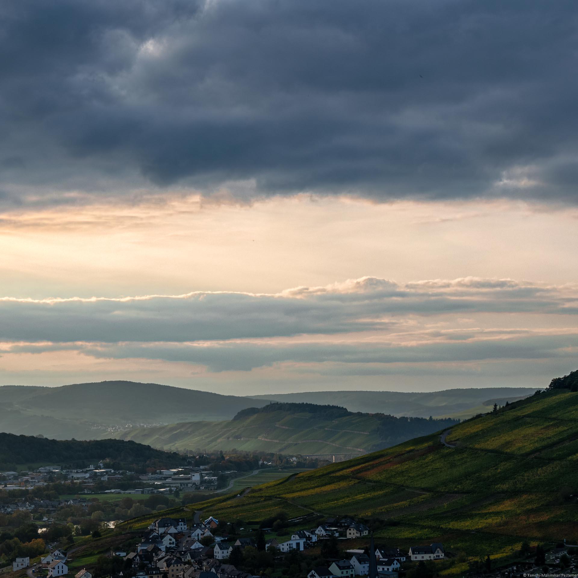 Im Vordergrund links befindet sich Bernkastel-Kues. Dahinter rechts liegt der Weinberg Kueser Weisenstein. Etwas weiter links liegt der Ortsteil Andel. Dahinter liegt der Weinberg Brauneberger Juffer Sonnenuhr. Es folgen weitere Weinberge und bewaldete Hügel. Der Himmel ist gelb-orange gefärbt. Oben erkennt man eine dunkel-blaue Wolke.