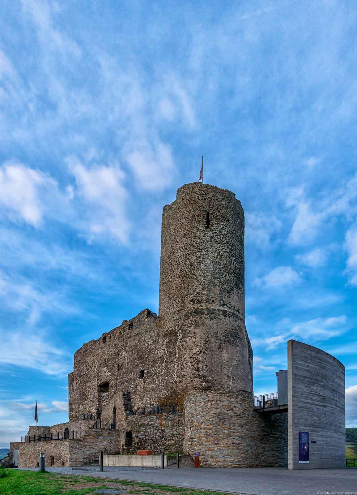 Oberhalb von Bernkastel-Kues liegt die Burgruine Grevenburg. Runde im die Grevenburg ist blauer Himmel mit einigen Wolken.