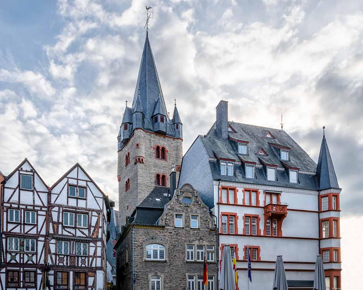 Vorne links ist ein Haus mit Fachwerk-Fassade. In der Mitte ist ein Haus mit Schiefer-Mauern. Rechts ist ein größeres weißes Gebäude mit roten Fensterrahmen. Das Dach ist aus blauem Schiefer. Dahinter ragt der Turm der Pfarrkirche St. Michael in den blauen und bewölkten Himmel von Bernkastel-Kues empor.