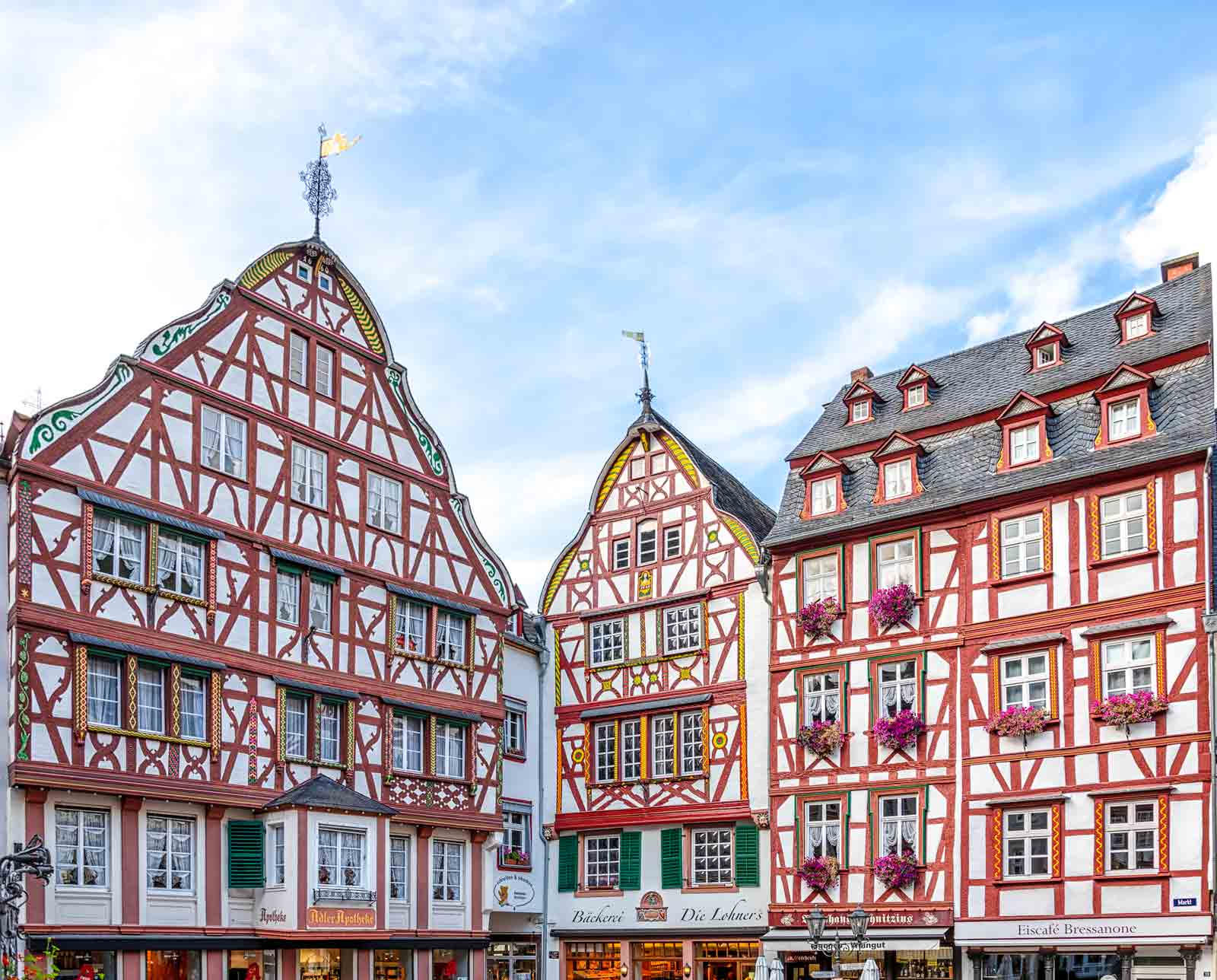 Man erblickt drei Häuser mit Fachwerk-Fassaden am Marktplatz von Bernkastel-Kues. Unten sind Läden. Am blauen Himmel sind Wolkenschlieren.