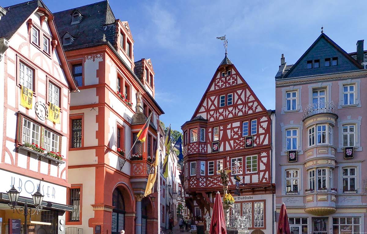 Man sieht Häuser am Marktplatz von Bernkastel-Kues rund um den Michaelsbrunnen. Die Häuser haben Fachwerk-Fassaden. Oben ist noch etwas blauer Himmel.