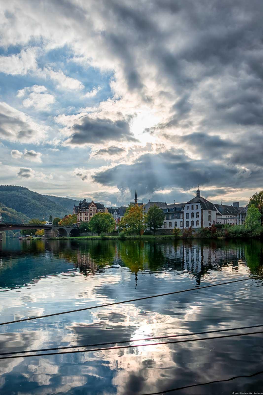 Im Vordergrund spiegelt sich das St. Nikolaus Hospital. Dieses ist auch als Cusanusstift bekannt und befindet sich am Ufer der Mosel in Bernkastel-Kues. Daneben erkennt man links in der Mitte eine Brücke und weitere Gebäude. Am hellen Himmel strahlt die Sonne durch die großen Wolken hindurch.