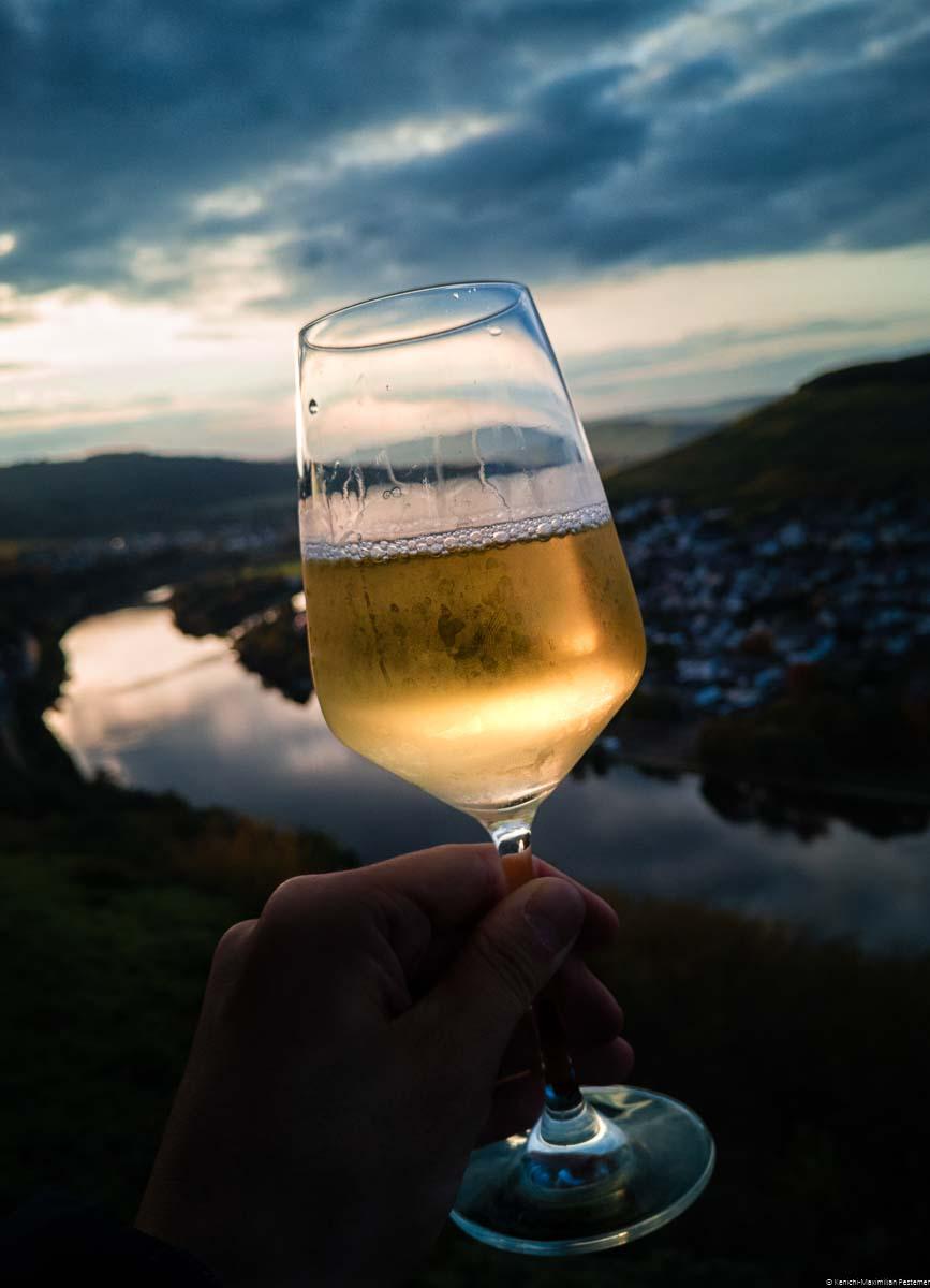 Am Abend wird ein Glas Riesling im Vordergrund genossen. Im Hintergrund befinden sich die Mosel, der Weinberg Kueser Weisenstein, weitere Weinberg und ein atemberaubender Sonnenuntergang.