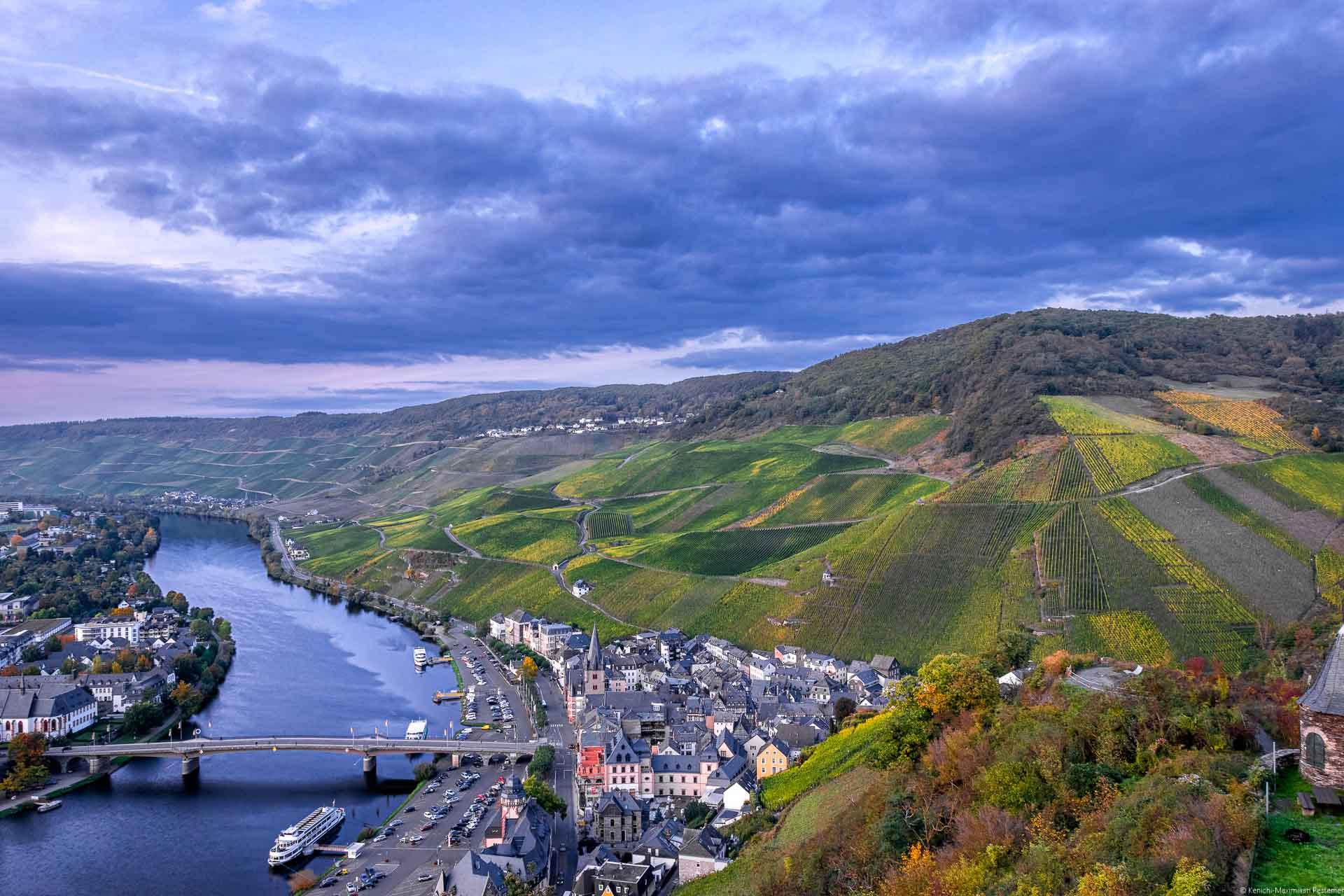 Am Abend blickt man auf den Ort Bernkastel-Kues, die Mosel und die dahinter liegenden Weinberge. Am Himmel sind lila Wolken.
