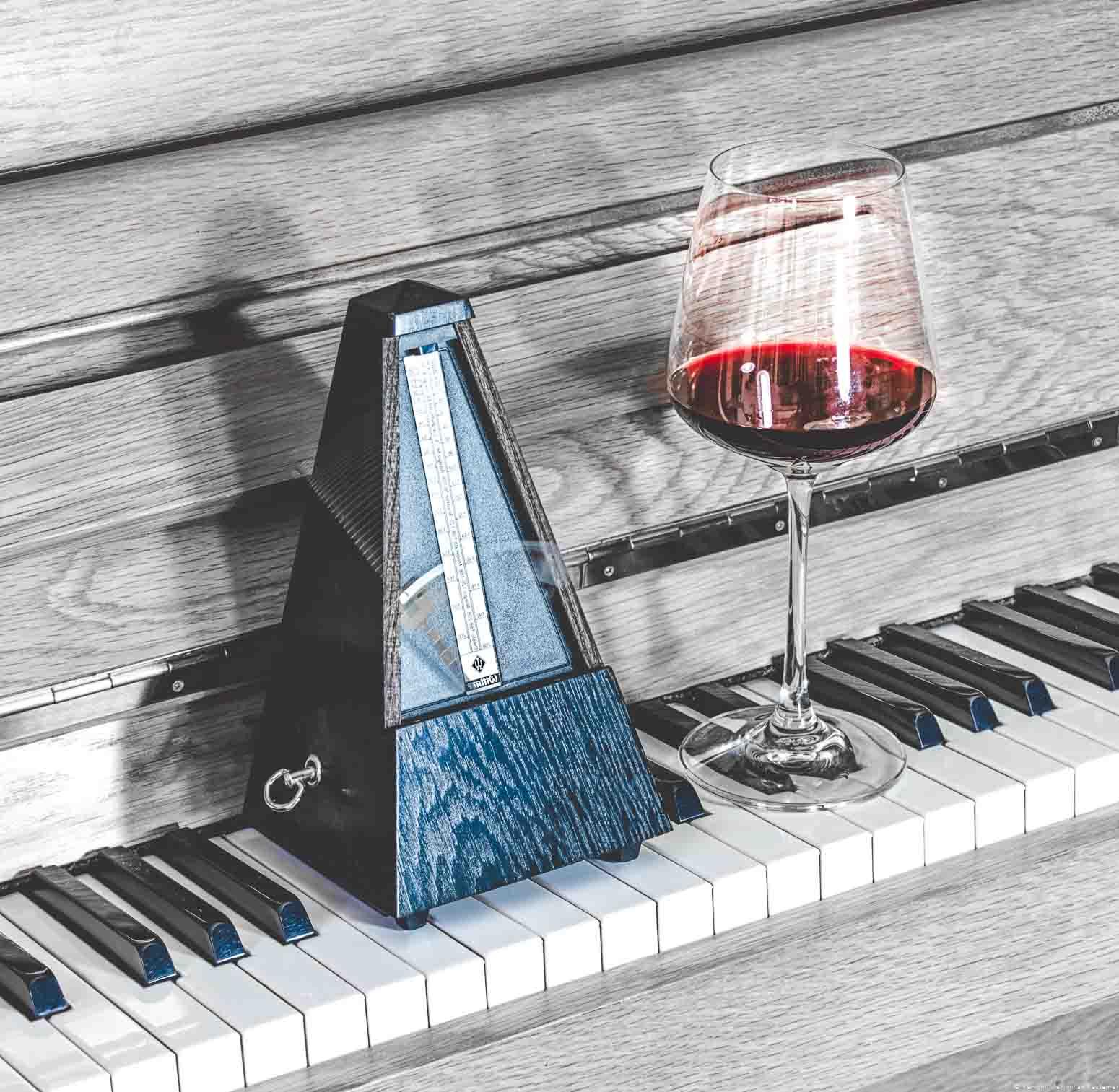 Schwingendes Metronom neben Glas Wein auf aufgeklappter Klaviertastatur
