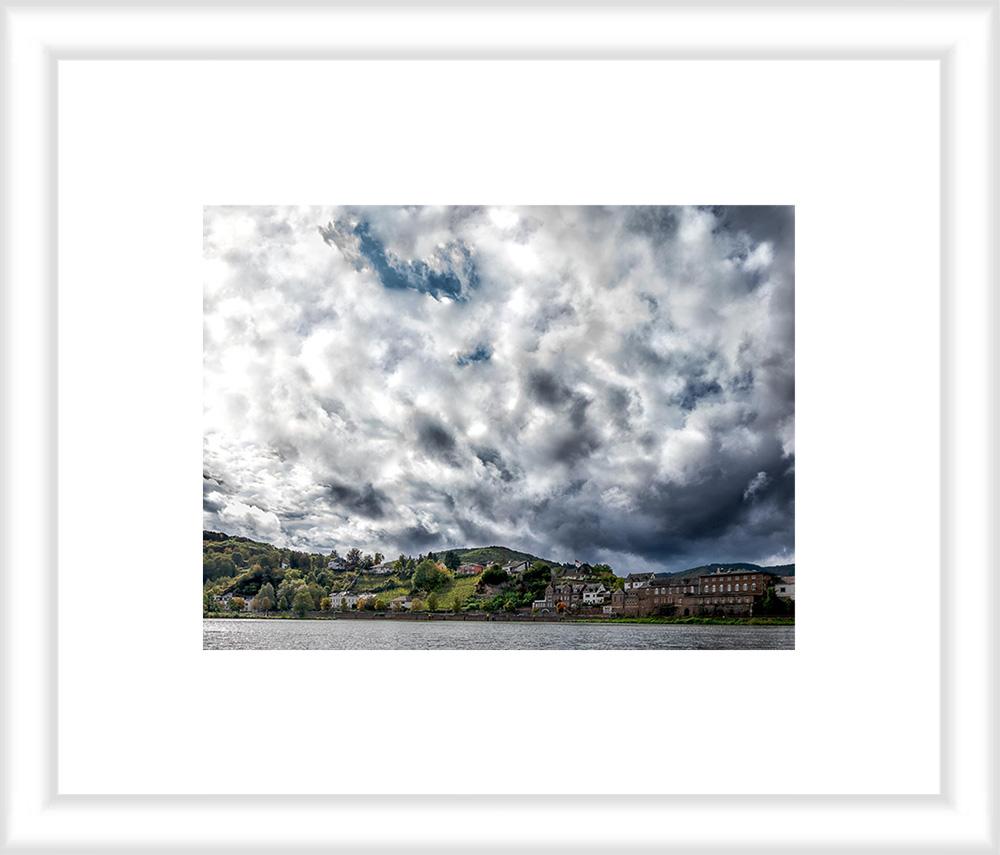 Bild mit weißem Holzrahmen und Passepartout: Im Vordergrund fließt der Fluss Mosel. Die Alfer Hoelle ist ein Weinberg der sich in den Ort Alf einfügt. Der Weinberg liegt an einem Hang zwischen Häusern am Ufer des Flusses. Der Himmel ist stark bewölkt.