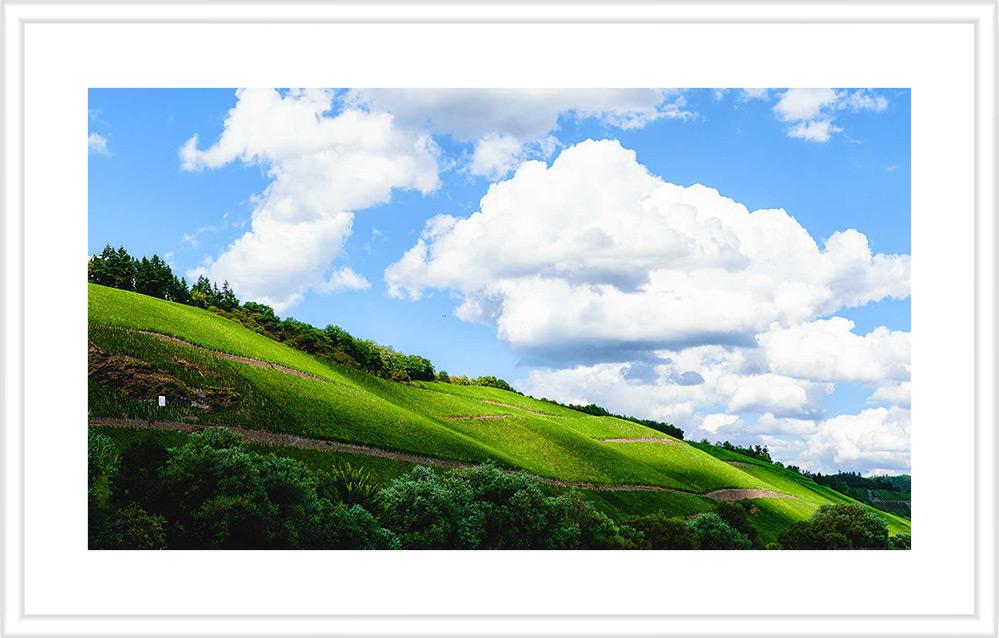 Bild mit weißem Holzrahmen und Passepartout: Steile Weinberge Brauneberger Juffer und Braunberger Juffer Sonnenuhr, bewölkter Himmel