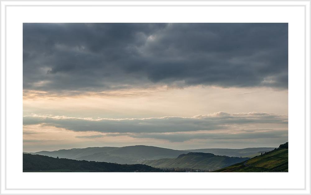 In der Mitte erkennt man den Weinberg Brauneberger Juffer Sonnenuhr am späten Abend. Links und rechts sind weitere Weinberge und bewaldete Hügel. Am Himmel sind blau-graue Wolken und eine orangene Färbung erkennbar.