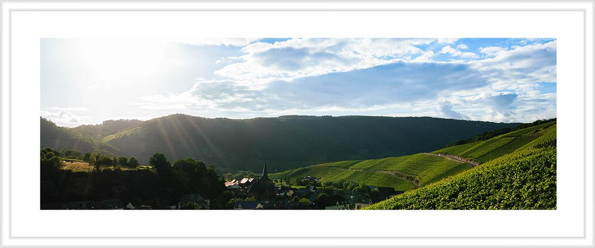 Bild mit weißem Holzrahmen und Passepartout: Auf der rechten Seite des Bildes wölbt sich der Weinberg Dhroner Hofberger in das Dhrontal hinein. In der Mitte des Bildes erkennt man den Ort Neumagen-Dhron. Im Hintergrund sind bewaldete Hänge und Wolken sowie die Sonne am blauen Himmel.