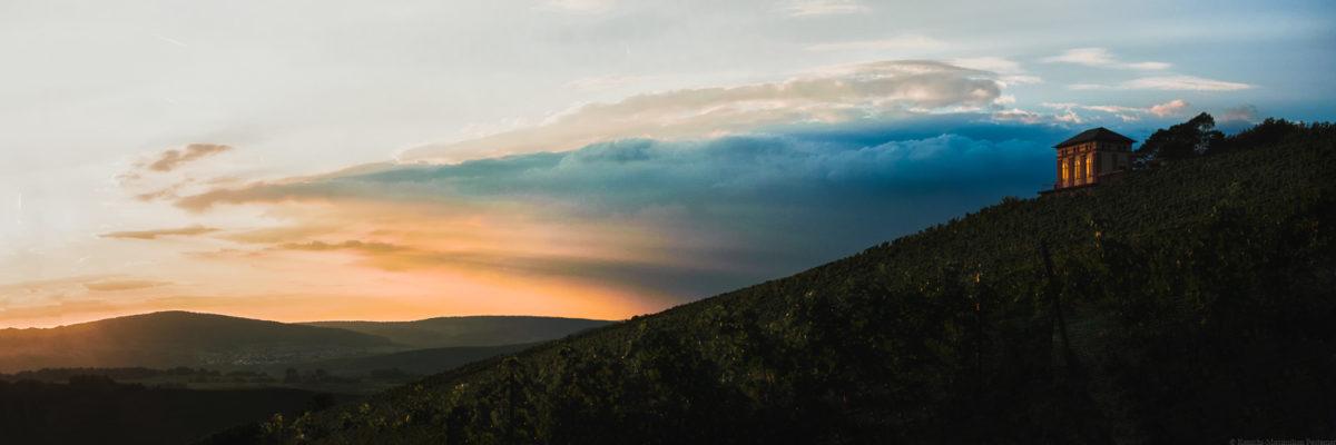 Auf der rechten Seite des Bildes ist ein kleines Häuschen am oberen Ende eines steilen Weinberges erkennbar. Es handelt sich um das sogenannte Elisenhäuschen auf der Weinberg Elisenberg. Auf der linken Seite blickt man in die Ferne des Moseltal Oben rechts am Himmel ist eine blau Wolke. Links ist die Wolke Orange und man erblickt viel Sonnenlicht am Abend.