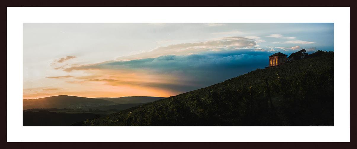 Bild mit Nussbaumrahmen und Passepartout: Auf der rechten Seite des Bildes ist ein kleines Häuschen am oberen Ende eines steilen Weinberges erkennbar. Es handelt sich um das sogenannte Elisenhäuschen auf der Weinberg Elisenberg. Auf der linken Seite blickt man in die Ferne des Moseltal Oben rechts am Himmel ist eine blau Wolke. Links ist die Wolke Orange und man erblickt viel Sonnenlicht am Abend.
