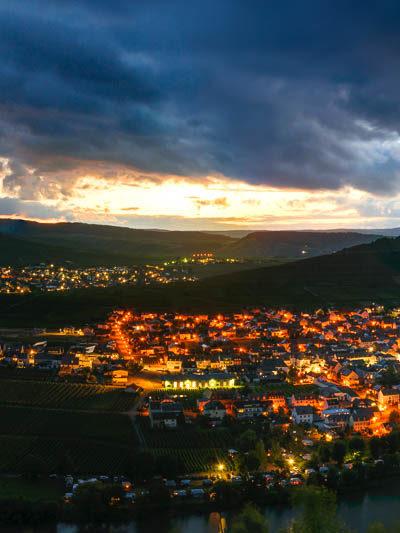 Vom Berg aus blickt man auf die Orte Trittenheim und Leiwen in der Nacht. Die Orte sind aufgrund des Lichts in Orange eingefärbt. Im Fluss Mosel spiegelt sich der stark bewölkte Himmel.