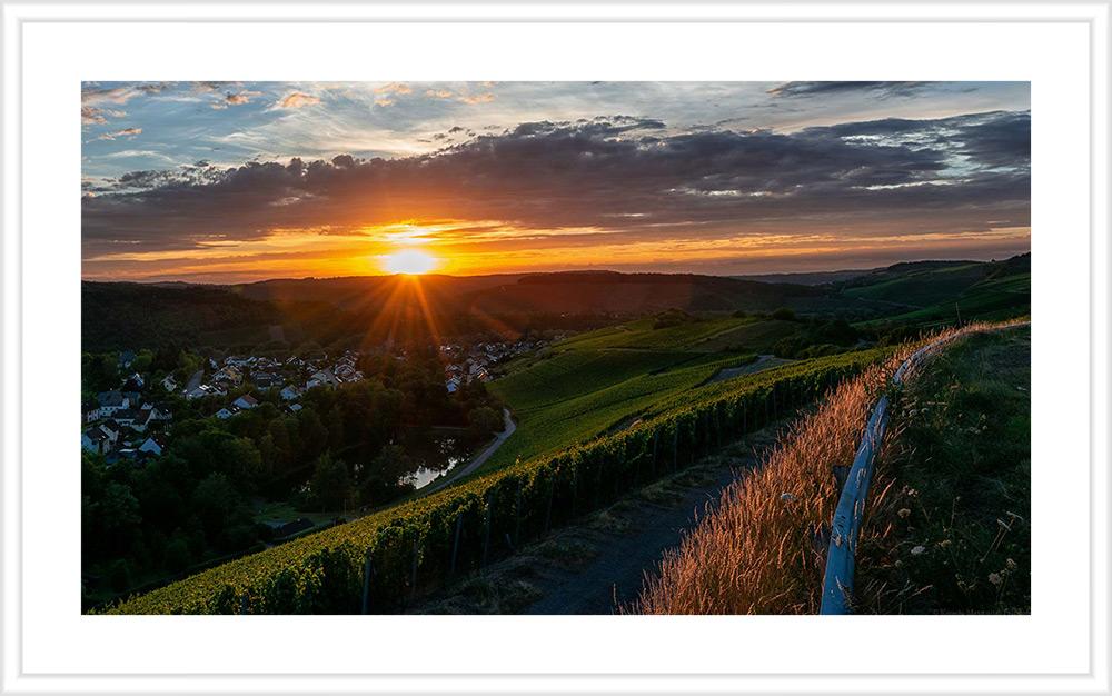 Sonnenuntergang am Weinberg Wiltinger Braunfels an der Parzelle Vols. Am Fuße des Weinberges fließt der Praweltsbach. Daneben liegt der Ort Wiltingen. Das Bild hat einen weißen Rahmen mit weißem Passepartout.