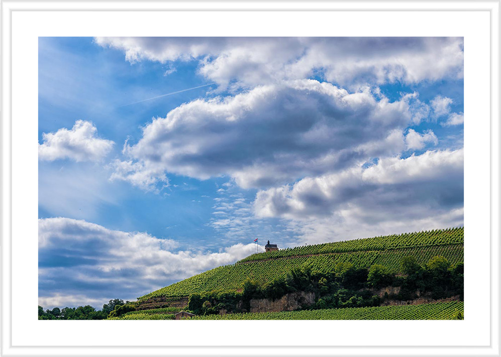 Bild mit weißem Holzrahmen und Passepartout: Weinberg mit Häuschen und Flagge Luxemburg bei sonnigem Wetter und einigen Wolken