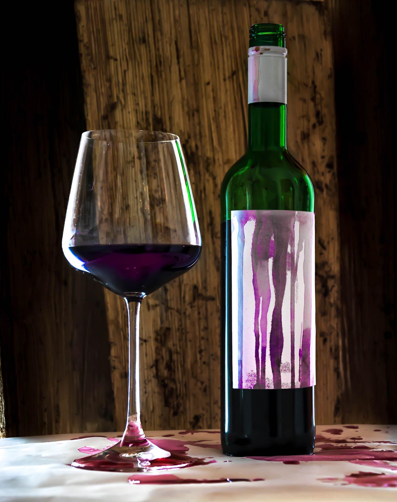 """Auf dem Bild ist links ein Glas Rotwein erkennbar. Rechts steht eine Flasche Schomlauer. Das Etikett der Weinflasche und der weiße Papierboden sind von Rotweintropfen bedeckt. Im Hintergrund ist Holz. Das Bild spielt auf Béla Hamvas Werk, """"Die Philosophie des Weins"""" an."""