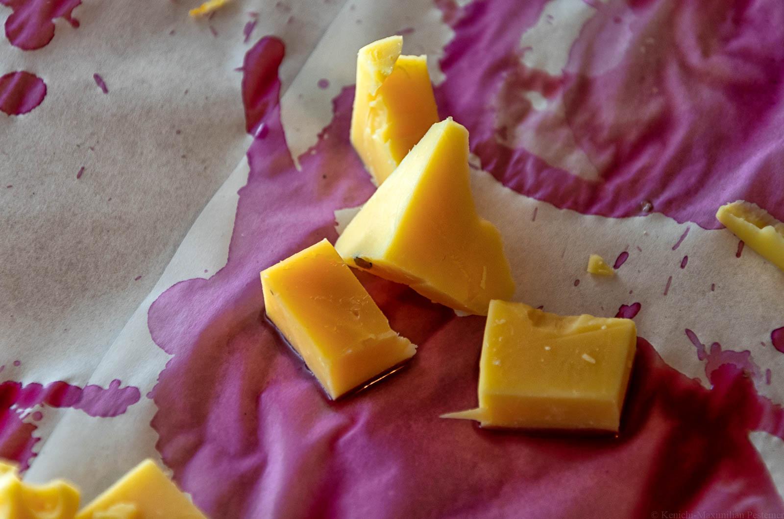 Käsestücke liegen auf mit Schomlauer-Rotwein getränktem Papier. Dies ist eine Hommage an Béla Hamvas Philosophie des Weins.